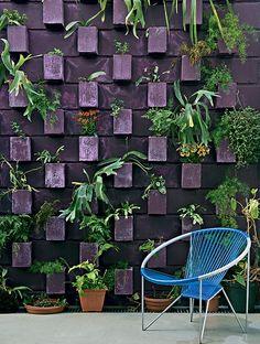 """Foi da moradora Stella Garçon a ideia dos jardins verticais para aproveitar melhor a área externa. """"Vi o painel de blocos virados com planta em um muro da av. Faria Lima e quis fazer igual aqui"""", conta. Pintados com tinta roxa, eles viraram vasos"""