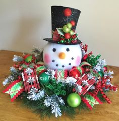 Large snowman head decoration for your holiday table. Snowy pine wreath with holiday ornaments, sparkly curly sprigs, make this arrangement a real stand out.  Two small sleds were added to this arrangement. Just what any snowman would love.  This is a large arrangement measuring approximately 27 in diameter and 20 tall. The snowman head is just wired in so he can easily be removed to be used as a tree topper at a later date.  The items in this wreath may be purchased separately----  Raz…