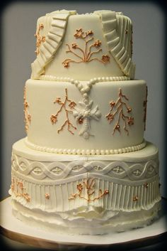 Christening cake- minus guilding, all white with the rosary in blue and the cross in gold.