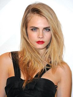 """Tousled hair, lush lashes, and red lips: It doesn't get much sexier than that. The deep side part—a change from Delevingne's usual center one—softens the effect, but the confidence comes down to the girl. """"Whatever you do to Cara, she owns it. She'll make it her own rather than have a look stamped on her,"""" says McKnight."""