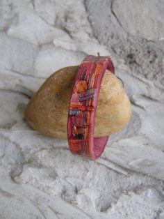Kožený náramek - malý Náramek je vyrobený z kůže a je zdobený / rytím / raznicemi vlisovaným vzorem / malováním / a dobarvený do červené. Délka 19,9 cm šířka1,3 cm. Zavazuje se na voskovanou šňůrku,takže je potřeba více uzlíků. Nemusí se zavazovat až nakonec,čímž můžeme volit délku náramku.