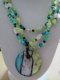 Lampwork glass disk pendant on a 3 strand necklace. Silver lined glass beads in aqua,lime green and silver with black accents.    SOLD