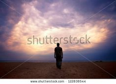 Man goes to the sea on dark sand beach under beautiful colorful cloudy sky by Eugene Sergeev, via Shutterstock