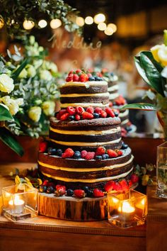 Three-tiered chocolate naked wedding cake with berries for rustic wedding