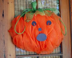 Deco mesh pumpkin with jack-o-lantern face.  Made with deco mesh and a work wreath form.