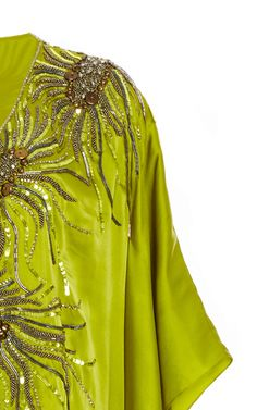 This **Pamella Roland** caftan features a v-neck, flutter sleeves, a relaxed silhouette with abstract beading at the front, and a floor length hem with splits at the sides.