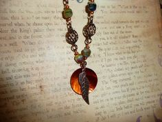 This necklace is a beautiful collection of antique copper chain and beautiful greenish brown check glass beads. Hanging as the center piece of this necklace is a brilliant fiery orange shell decorated with an antique copper feather. This necklace is complete with a magnetic clasp that allows for easy application.