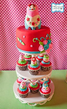 Matryoska (Russian Nesting Doll) Cake & Cupcakes  I love the fun & funky colors and the vines coming up out of the bouquet on the side :)