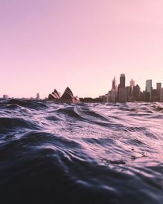 reflection, sunset, city, architecture, urban skyline, built structure, sea, clear sky, building exterior, cityscape, skyscraper, water, pink color, travel destinations, surface level, sky, outdoors, no people, nature, downtown district, wave, bridge - man made structure, beach, day, yacht