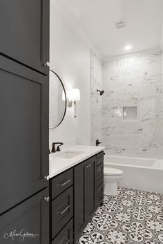 Classic black and white with a modern twist! The neutral pattern tile complements the marble veining to create a timeless and unique space. Did we mention that we love a bold cabinet color? 🏠: Daniel Michaels Builder, Inc. . . . #unitedtileco #danielmichaelsbuilder #newconstruction #patterntile #bathroominspo #interceramic #marblelook #rickerttile #blackandwhite #classiccolors Bathroom Inspo, Cabinet Colors, Porcelain Ceramics, Tile Patterns, New Construction, Marble, Neutral, Black And White, Mirror