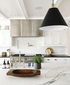 kitchen with oversized black pendant lighting over white marble island