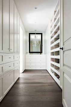 Walking into a long walk in closet you'll see a white dresser with a black mirror overhead.