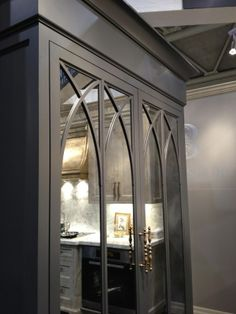 Decorative scissor arches in cabinet fronts with smoked mirror on fridge. Bloomsbury Cabinetry, designed by Brian Gluckstein. (Meredith Heron Design IDS Toronto 2012)