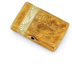 A Gold Samorodok Cigarette Case  Maker's mark 'AH', St Petersburg, 1908-1917  Rectangular with rounded sides, the body and cover chased with a band of partially opened fan motifs, the cover with cabochon sapphire thumb-piece, marked inside body and cover  3 7/8 in. (9.8 cm.) wide,  Christie's n°7906.