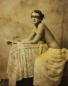 Black and white sepia photo of a woman wearing painted on mask, nude, with glass of wine and holding a card