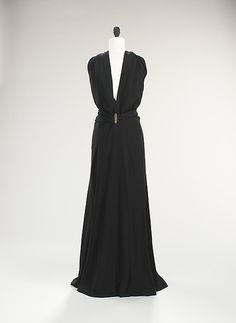 (Back Side) Evening dress | Madeleine Vionnet 1936 | Vionnet creates both a fluid skirt and inventive bodice with panels that frame a plunging back, then extend over the shoulders to be gather in a pleated drapery detail. The sinuous line and cutaway exposures of the dress make it an excellent example of the period.