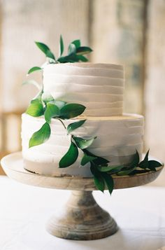 A simple all white cake with greenery