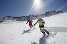 Couple skiing down a piste