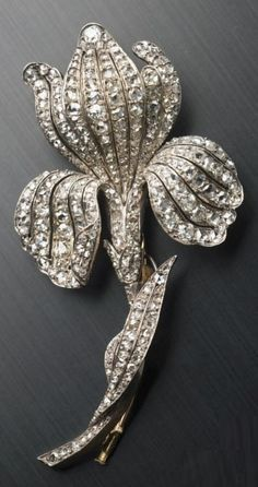 An elegant antique silver and diamond brooch, second half of the 19th century. Designed as a stylised iris, set throughout with rose- and old-cut diamonds, mounted in silver. #antique #brooch
