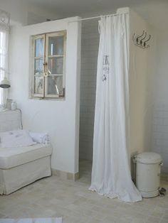Ungewöhnliche Bad Einrichtungsidee mit einer extra Portion Gemütlichkeit in Weiß! Begehbare Dusche toll eingebracht mit Sprossenfenster und Vorhang.