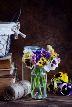Pansies in glass bottles, a ball of twine and old books on a wooden background