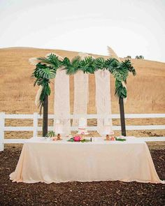 A Boho California Wedding with a Tropical Twist | Martha Stewart Weddings - Macramé table runners hung behind a trio of cakes made by Paper Cake Events. Palm leaves were then affixed to the structure holding the textiles to tie it all together.