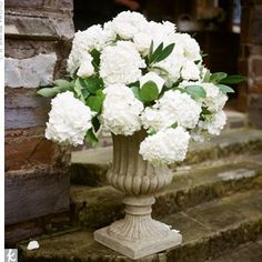 The ceremony site will feature two large urn vases with spilling cream hydrangeas, seeded eucalyptus, variegated pittisporum, peachy-pink spray roses, and jasmine vine.