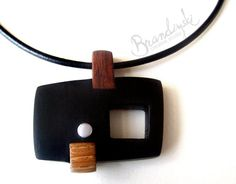 This is original handmade wooden necklace, made from 3 different exotic woods. Black ebony, brown ebony and oak wood. With aluminum detail and 3mm leather cord.  Unique design. Impregnate wit teak oil to save the color and softness of the wood.  Made to bring esthetic pleasure and sense of something unique and unrepeatable.    Cord ID: 3mm  Pendant size: 5.3 cm x 5.0 cm / 2.1 in x 2.0 in