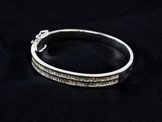 Diamond baguette bangle containing two rows of calibre set baguette cut diamonds as hinged bangle of unhaalmarked white gold stamped 750. Diameter 5.5cm. Gross weight 31.3 grams.  Estimate £ 800-1,200