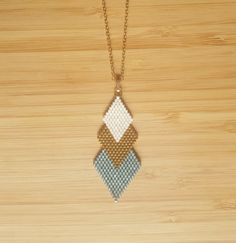 Saltire gilded end 14 carats (plating gold filled) and weaving in glass beads Miyuki from Dark Aqua color iridescent, white broken mat and gilded in 24-carat gold. Chain 70 cm length.