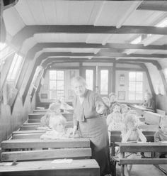 """Caption: """"A teacher explains a point to one of her pupils at a #school held on board an old #canal #barge on the Grand Union Canal at Hayes in #Middlesex. There are several places along Britain's canal network where special schools cater for """"boatmen's children"""". This site in Hayes is where the Grand Union Canal Carrying Company have their repair and maintenance shops and """"when the boats are in for maintenance or overhaul, or are resting between trips, children attend the school"""".  #elsdale"""