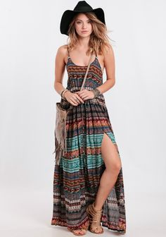 Super rad flowy maxi dress featuring an allover paisley and floral print in hues of teal, light-pink, burgundy, and mustard. Finished with skinny shoulder straps, a drawstring waist, and a thigh-...