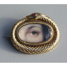 LOVER'S EYE 14K GOLD SERPENT OUROBOROS BROOCH. Glazed oval quarter face portrait encircled by serpent with ruby eye , ca. 1820.