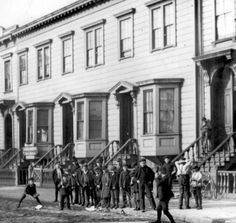 Children play ball in the street in front of typical housing with five rooms per family for $10 to $12 per month. San Francisco, ca. 1900.