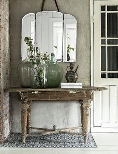 vintage demijohns on french winemakers table rustic farmhouse entryway