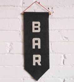 Let folks know where you keep the whiskey by hanging up this helpful handmade sign. The pointed felt shape and vintage-inspired letters are cut and arranged vertically by hand, the finished banner suspended from a wood dowel and red cord for hanging.