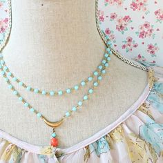 This lovely necklace is made with a double bead chain in pale aqua with 6mm glass beads, the longer strand is connected to a little golden brass crescent with a