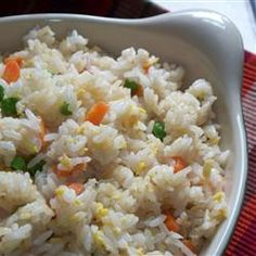 Fried Rice  INGREDIENTS:  2 cups enriched white rice  4 cups water  2/3 cup chopped baby carrots  1/2 cup frozen green peas  2 tablespoons vegetable oil  2 eggs  soy sauce to taste  sesame oil, to taste (optional)