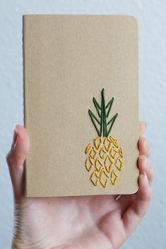 Una piña es bordada con hilos de color amarillos y verdes mostazas en un cuaderno forrado kraft marrón, ideal para la elaboración del plan de verano. Mantenerse organizado sólo llegó a ser un poco más divertido con este cuaderno bordado de mano. Un tamaño perfecto para caber en el bolso, listo para llenar con sus dibujos y listas. Cuaderno: 3.5 x 5.5 pulgadas Páginas: 64 Encontrar más aquí: https://www.etsy.com/shop/PoppyandFern?section_id=14287899