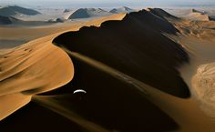 Dasht-E Lut • Irã O francês Alain Arnoux conduz seu paraglider motorizado em meio a ventos traiçoeiros acima de uma enorme duna no deserto de Lut, no Irã. Campeão nessa modalidade de voo, Arnoux colaborou com o fotógrafo George Steinmetz em mais de uma dúzia de expedições