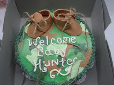 """This was a camouflage cake with """"desert booties"""" that I made for a baby shower. I don't care for the whole idea of anything camo for anything BABY, but to each his own, I guess! I really need to practice my cake writing, but they loved it anyway!  It was French vanilla with a raspberry glaze filling."""