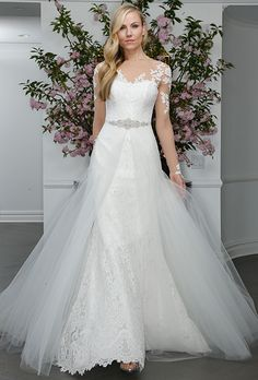 Brides.com: . Lace wedding dress with an illusion neckline and tulle overskirt, Legends Romona Keveza