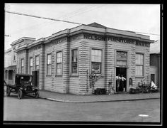 G. P. Russell & Sons, Nelson Furniture Mart. View of the Nelson Furniture Mart building on the corner of Collingwood and Bridge Streets. Two men stand in the doorway and a truck is parked on the street outside.