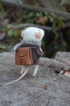 This is a cutie picture of a mouse wearing a knitted scarf, and a little brown backpack.