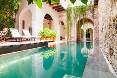 Colombia vacation rental // heavenly pool with stone walls and green ivy on building