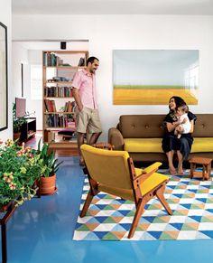 Rodrigo Oliveira com a mulher, Helena, e a filha, Dora. ccSobre o piso, tingido de epóxi azul, destaca-se o tapete geométrico (Square Foot). Sofá do Fernando Jaeger Atelier e poltrona da Loja Teo. Na parede, foto África, do 8 Coletivo (1 x 1,50 m, na Democrart).