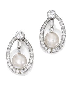 PAIR OF NATURAL PEARL AND DIAMOND EARCLIPS. The swing centers anchored by two natural pearls measuring approximately 10.9 by 10.5 by 9.1 mm and 10.7 by 10.6 by 9.5 mm, suspended and framed by baguette, old European and single-cut diamonds weighing approximately 4.15 carats.
