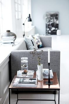 copper table, green-grey wall, while floors, grey couch and the lamp, light room ...<3...