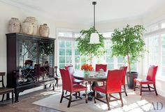 Punchy red leather chairs surround the table in Ben Soleimani's sun-drenched breakfast room