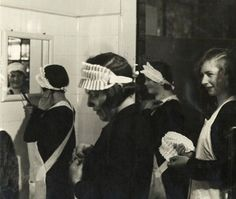 Hotel maids getting ready for work in a bathroom, 1920s. | The ...